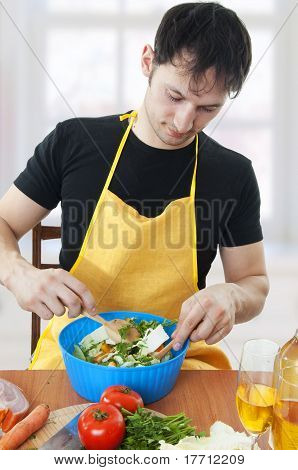 Young Handsome Man Cooking Salad
