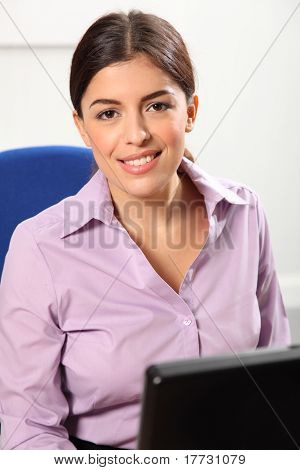 Smiling woman at computer in office