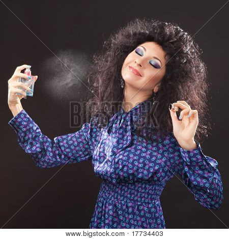 Young fashion woman with perfume on black background