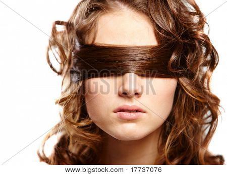 Portrait of woman covering eyes by her hair