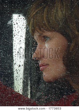 Niña mira a través del vidrio de la viuda de Waterdropped 9