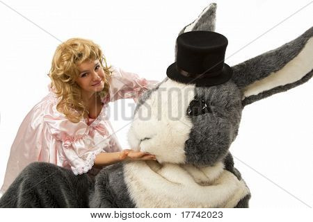 Close-up portrait of a pretty girl in pink dress with a big grey fur's color rabbit against white background