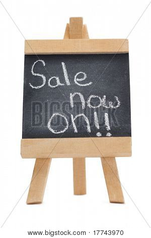 Chalkboard with the words sale now on written on it isolated against a white background
