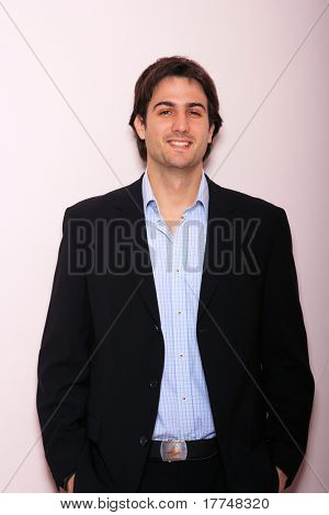 Young business man standing against the wall with hands in pocket