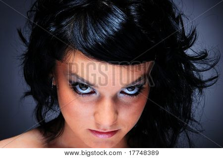 Portrait of glamour woman with evil look over dark gray background
