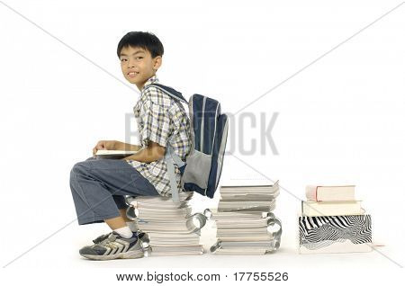 Young boy sitting on a pile of books on white