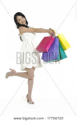 Una hermosa chica asiática llevar bolso de compras