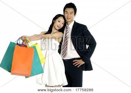 Shopping couple smiling on white