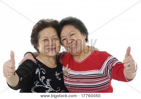 Two senior lady giving two thumbs up. Isolated on white