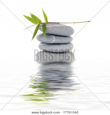 Stacked pebbles & bamboo leaf with reflection