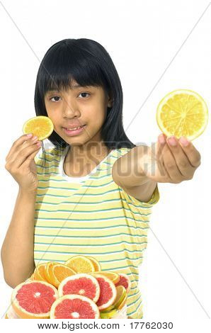 Cute girl playing with oranges and slices grapefruit