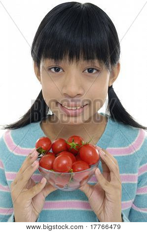 Close up young girl holding bowl of fresh tomatos
