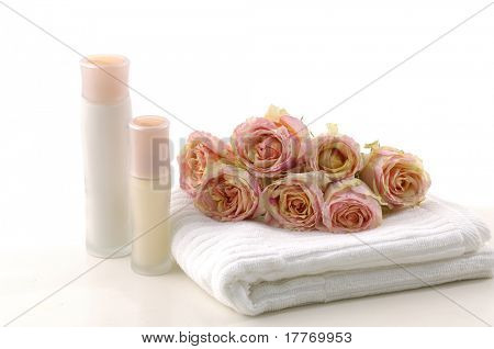 Spa essentials. Towel, bottle with oil and pink rose