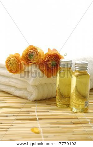 spa essentials- ranunculus flowers on towel and massage lotion,