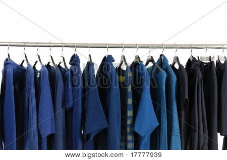 A row of designer fashion clothing hanging on hangers