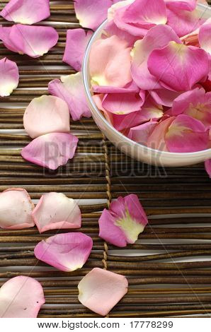 Bowl of rose petals on bamboo spa mats