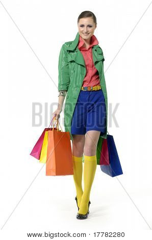 girl walking and smiling while carrying shopping bags