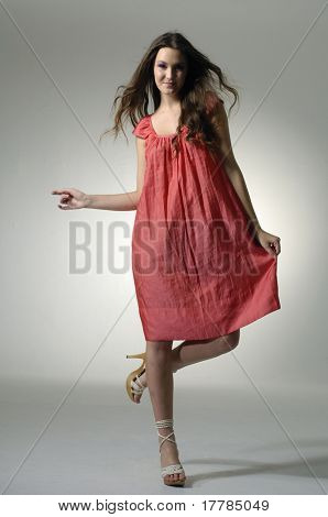 Beautiful girl in red dress dancing on light background