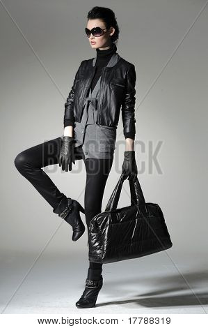 High fashion model with bag posing in the studio