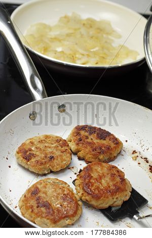 On a black glass stove top two pans are being used to cook dinner. In one pan are four turkey burgers cooking and in the back pan are white onions being simmered