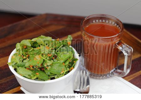 Bowl of ginger carrot tomato watercress salad with a cup of tomato juice. Lunch of watercress salad and a mug of tomato juice on a beautiful wood tray.