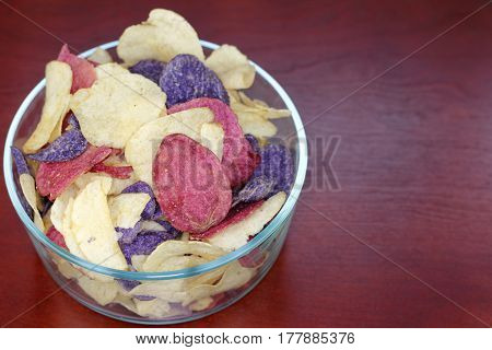 Crimson Yellow and Purple Potato Chips Crimson Purple Majesty and Chipeta or Atlantic potato chips in a glass bowl on a wood table. Potato chips variety mostly referred to as red white and blue.