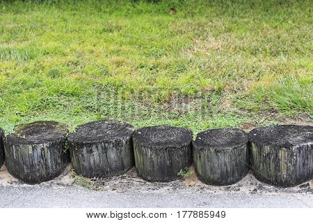 Wooden tree logs partly buried in the ground together as a wall to help prevent soil erosion. Part of a soil erosion barrier made from tree logs in a grassy area.