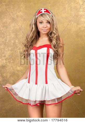 sexy blonde woman in seductive nurse costume on golden background