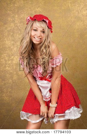 sexy blonde woman in red vintage dress on golden background