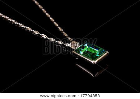 Square pendant with green gem isolated on black