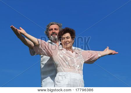 old man and woman standing, smiling and looking at camera, hands apart, blue sky