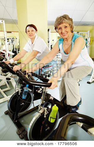 Portrait of senior females doing physical exercise on special equipment in club