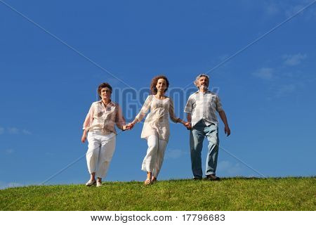 adult daughter and her parents holding for hands and walking on lawn