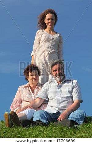 adult daughter and her parents on summer lawn, blue sky, focus on parents