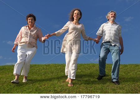adult daughter and her parents holding for hands, smiling and walking on lawn