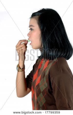 Jovem asiática estava comendo uma cápsula do comprimido