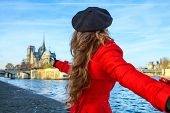 Woman Holding Friends Hand And Pointing At Notre Dame De Paris poster