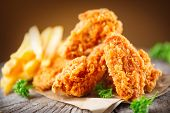 Fried chicken wings on wooden table. Breaded Crispy fried kentucky chicken tasty dinner. poster