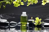 tranquil spa scene - massage oil and candle on black stones with green orchid
