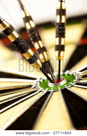 Cut image of dart pierced on target over dartboard