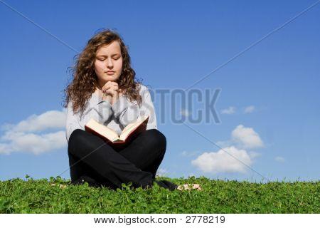 Child Reading Bible And Praying