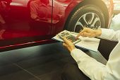 This Career Salesman Calculating On Calculator Car Price In Showroom Car.close Up Tire Red Car In De poster