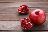 Pomegranate And Half Of Ripe Pomegranate On A Grey Background poster