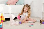 Adorable Kid Playing With Rabbit Toy And Plastic Cups In Children Room poster