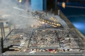 Chicken Wings On Barbecue Grill With Fire. Grilling Chicken Wings On Barbecue Grill. poster