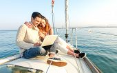 Young Couple In Love On Sail Boat Having Fun Remote Working At Laptop- Happy Luxury Lifestyle On Yac poster