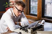 Writer At Work. Handsome Young Writer Wearing Glasses And White Shirt Sitting At The Table And Think poster