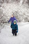 The Boy Runs Away From His Mother On A Snowy Path. The Boy Walks With His Mom On A Snow Covered Fore poster