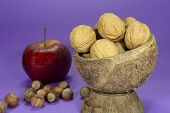 Whole Common Walnuts With Shells In Natural Coconut Shell Cup, Pile Of Whole Hazelnuts And Red Apple poster