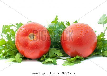 Dois tomates maduros com gotas de água e alguns salsa